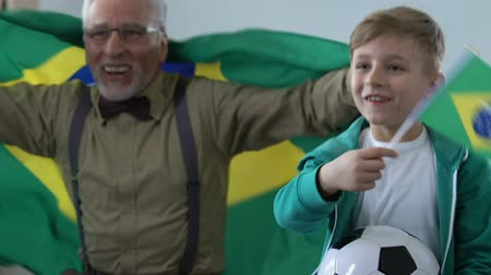 family watching tv : Old man with grandson supporting Brazil football team tv match.