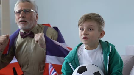 schoolkid : Cheering English fans celebrating football team goal, spending time together