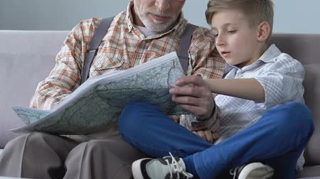 unokája : Retired man showing his travel places to grandson on map, planning trip together