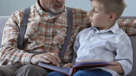memories photos : Senior man showing album photos grandson, telling life story. Stock Footage