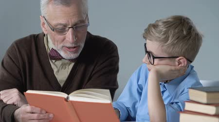 преподаватель : Old man reading book for grandson, helping with homework, spending time together Стоковые видеозаписи