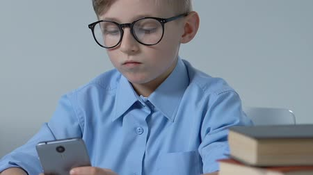 livro : Adorable school boy in glasses playing smartphone game in classroom during break