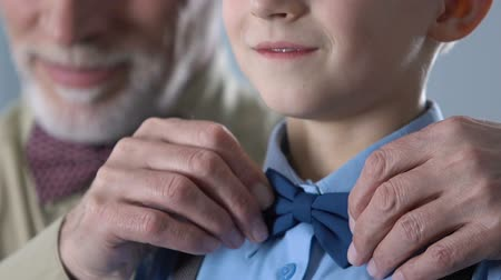 parentes : Grandfather adjusting grandson bow-tie, getting ready for concert, retro style