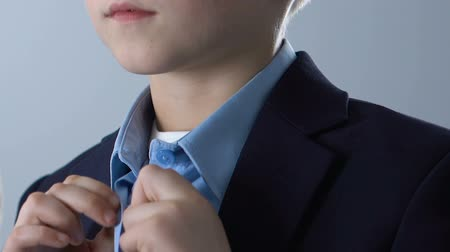 getting ready : Adorable boy buttoning up blue shirt, getting ready for school, child fashion Stock Footage