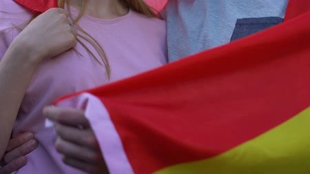 actively : Spain football team supporters, couple in love hugging, holding Spanish flag Stock Footage