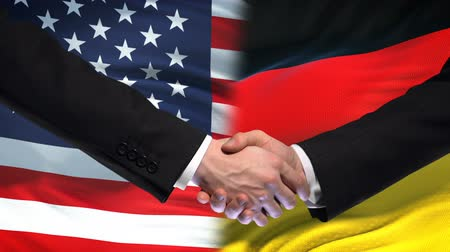 глобализация : United States and Germany handshake, international friendship, flag background