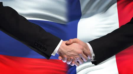 mutuo : Russia and France handshake, international friendship summit, flag background