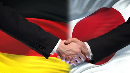 ministros : Germany and Japan handshake, international friendship relations, flag background