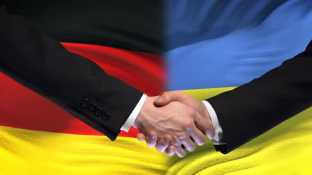 saygı : Germany and Ukraine handshake international friendship relations flag background