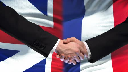 ministros : Great Britain and France handshake, international friendship, flag background