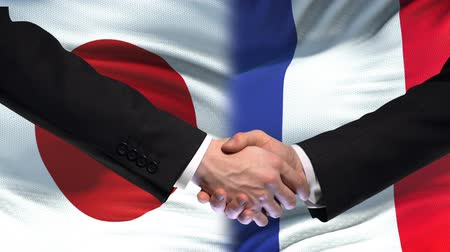 importação : Japan and France handshake, international friendship relations, flag background