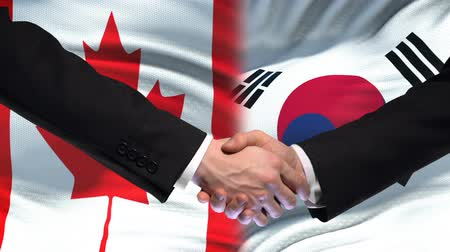 saygı : Canada and South Korea handshake, international friendship, flag background