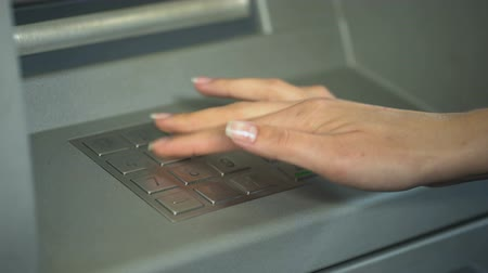 дебет : Woman entering PIN number to check bank account and withdraw money from ATM