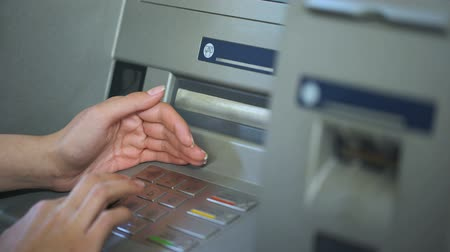 card pin : Lady hiding keyboard of automated teller machine while inserting her pin code