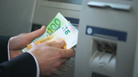 geri çekilme : Man counting euros withdrawn from ATM, putting cash in wallet, convenience Stok Video