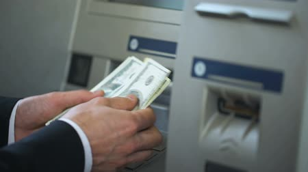 идентификация : Man counting dollars withdrawn from ATM, putting cash in wallet, 24h service