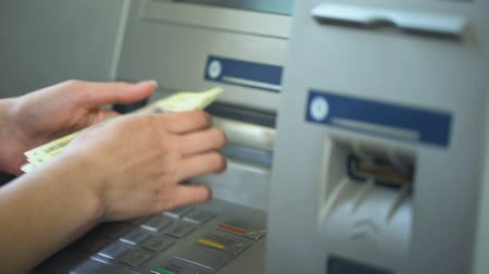 card pin : Woman counting Russian rubles withdrawn from ATM, putting cash in pink wallet