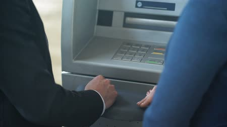 card pin : Female bank employee showing new client how to work with ATM, good service