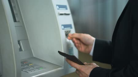 必要 : Business man inserting credit card in ATM, entering pin code to receive money