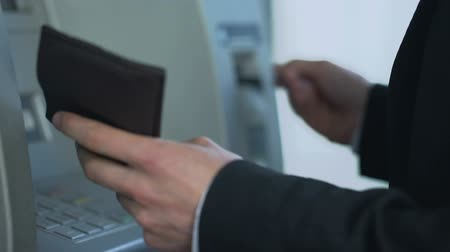 card pin : Male inserting card in ATM to withdraw cash and receive account balance report