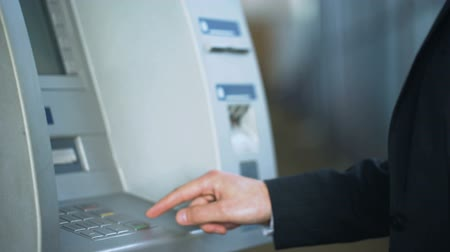 インサート : Male hands entering pin code on ATM keyboard, withdrawing money from account