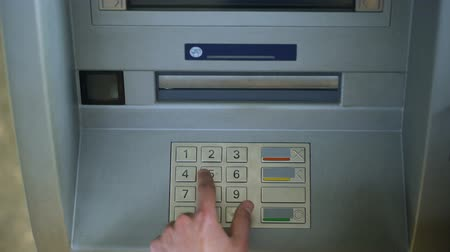 bankomat : Man entering PIN number on ATM keyboard, banking transaction top view, money