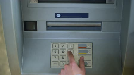 штифт : Man correcting pin code on ATM keyboard, transfer funds between bank accounts