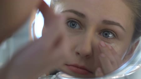 soft tip : Young woman applying eye cream, anti-age cosmetic. Stock Footage
