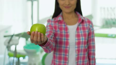 plaketa : Friendly girl offering apple in dental office, healthy teeth concept, vitamins Dostupné videozáznamy