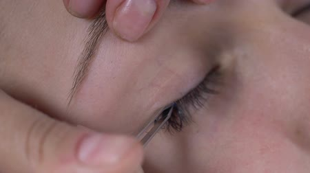 склеивание : Make-up artist gluing plastic eyelash extension with tweezers on customer eye