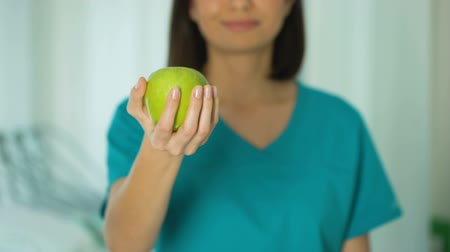 rekomendacja : Female doctor offering green apple, healthy lifestyle diet concept, dental care