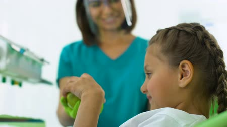 sensível : Woman dentist giving apple to girl, recommendations from specialist, oral health