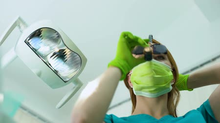 sterilità : Young woman dentist in magnifying glasses examining oral cavity, patient POV Filmati Stock