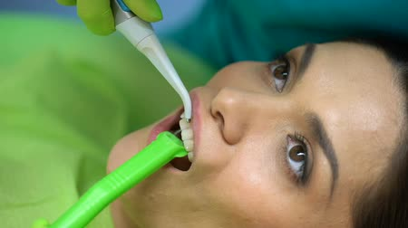 dor de dente : Dentist washing blue gel out from tooth, cosmetic dentistry, professional help
