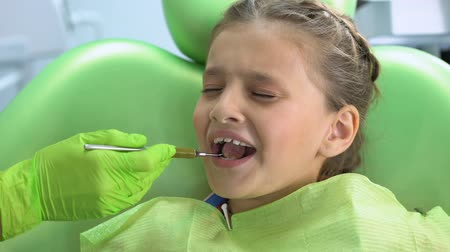 plaketa : Little girl afraid of dental checkup with mouth mirror, childish fear, stress Dostupné videozáznamy