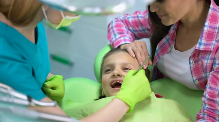 rendes : Child afraid of dental examination, doctor and parent calming little girl