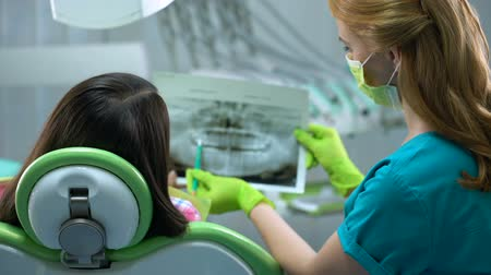 зубная боль : Dentist and patient watching teeth x-ray image, cavities, periodontal disease