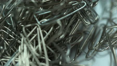 зажим : Metal paper clips stacked up extreme closeup, office supplies, unorganized group