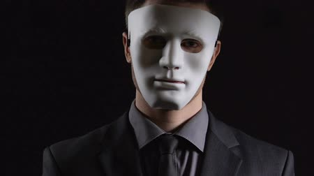 evasion : Anonymous suit man in mask folding hands on black background, illegal activity