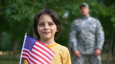 gururlu : Adorable boy holding american flag, male soldier standing behind, safe future