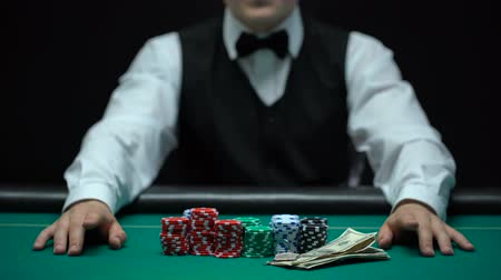 unlucky : Casino dealer waiting for bet, chips and money lying on table, gambling business