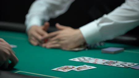 croupier : Croupier taking all chips and money, upset poker player showing empty purse