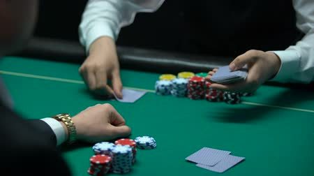 croupier : Male croupier dealing cards, player looking at bad combination, pair of deuces