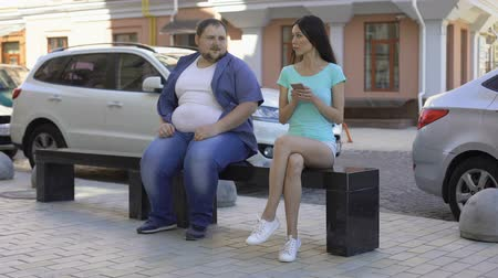 ignore : Slim woman ignoring overweight man, social rejection, obesity prejudices health