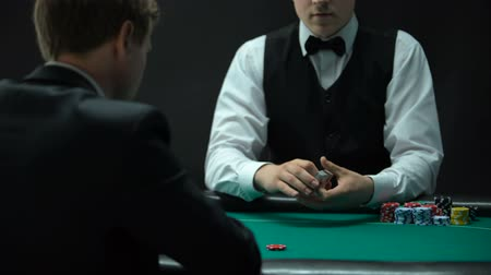 se zaměřením : Experienced croupier making shuffling tricks and dealing cards, chance to win