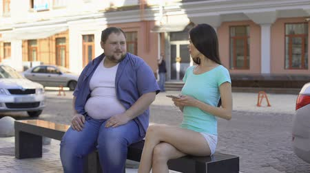denemek : Fit beautiful woman ignoring fat man sitting on bench, sad unconfident bachelor Stok Video