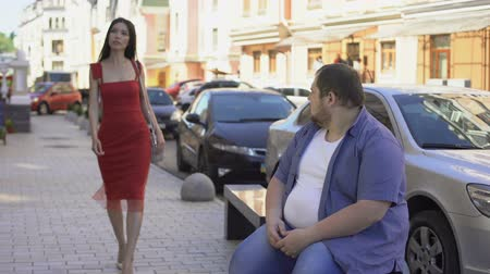 obyčejný : Obese male looking at beautiful elegant woman, lifestyle difference, motivation Dostupné videozáznamy
