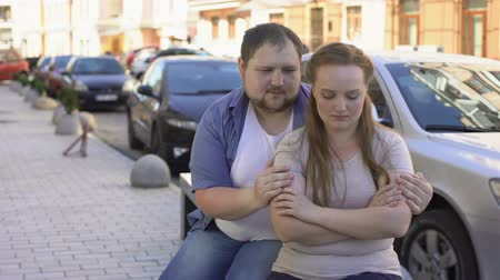 obesity : Guilty man making up with upset girlfriend, sitting on street bench, quarrel