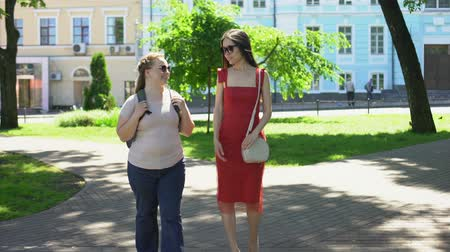 rendes : Fat and slim female friends walking park and talking, body contrast, diet