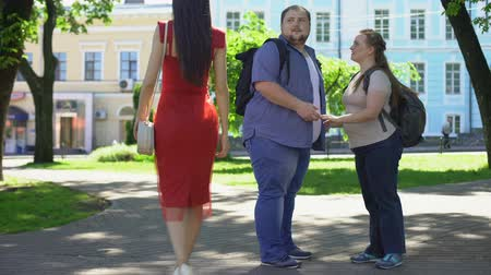 jealous : Fat man looking at beautiful lady in red passing by, obese girlfriend jealous